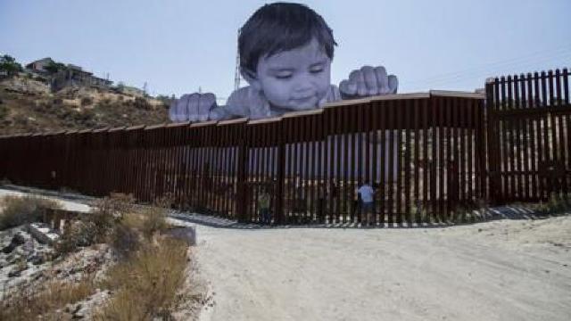 La graniţa dintre Mexic şi SUA a fost amplasată o fotografie uriașă a unui copil care se uită peste gardul despărţitor (FOTO/VIDEO)