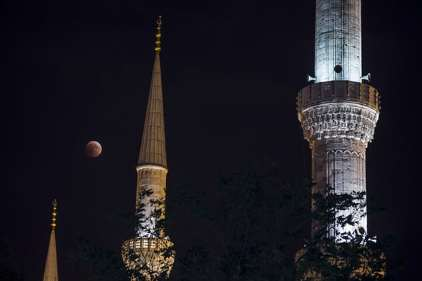 The blood moon appears to dangle between minarets in Istanbul, Turkey. Photograph: Anadolu Agency/Getty Images