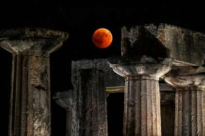 The full moon sits over the temple of Apollo in Corinth, Greece. Photograph: Valerie Gache/AFP/Getty Images
