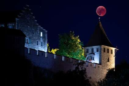 Here the moon appears as a giant weathervane on top of the Castle Luafen's turret, in Switzerland. Photograph: Melanie Duchene/EPA