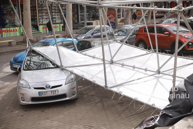 FOTO | Automobile parcate în fața Palatului Național, avariate după ce o construcție publicitară s-a prăbușit peste acestea
